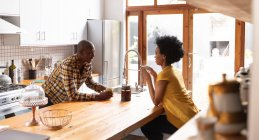Side view of an African American couple at home in the kitchen, sitting on either side of the kitchen island, drinking coffee and talking — Stock Photo