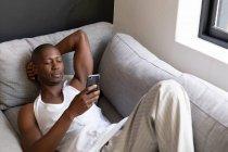 Вид спереди на афроамериканца в белом жилете, лежащего на диване с помощью смартфона в гостиной — стоковое фото