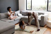 Вид спереди на афро-американскую пару и их маленькую дочь, отдыхающую в гостиной вместе утром, дочь, сидящую на полу, ее отец, разговаривающий с ней, и мать, сидящая на диване — стоковое фото