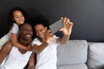 Вид спереди на афро-американскую пару и их маленькую дочь, отдыхающую в гостиной вместе утром, пару, сидящую на диване с дочерью, стоящей позади ее отца с руками на шее — стоковое фото