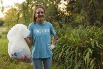 Портрет щасливої кавказької жінки - добровольці, які прибирають ліс у сільській місцевості, тримають мішок з сміття, посміхаючись до фотоапарата. Екологія і соціальна відповідальність в сільському середовищі. — стокове фото