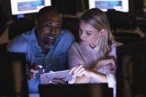 Mulher de negócios caucasiana e empresário afro-americano trabalhando tarde da noite em um escritório moderno, sentado em uma mesa, usando um smartphone, discutindo seu trabalho. — Fotografia de Stock