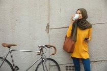 Mulher de raça mista vestindo hijab e jumper amarelo para fora e mais ou menos em movimento na cidade, em pé à beira da parede beber café takeaway segurando moto smartphone ao lado dela. Estilo de vida moderno Commuter. — Fotografia de Stock