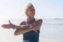 Старшая белая женщина с светлыми волосами, наслаждающаяся тренировками на пляже в солнечный день, практикующая йогу и растягивающаяся с морем на заднем плане. — стоковое фото