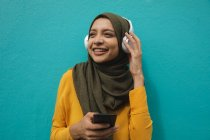 Mulher de raça mista vestindo hijab e jumper amarelo para fora e sobre em movimento na cidade, sorrindo segurando smartphone com fones de ouvido sem fio em. Estilo de vida moderno Commuter. — Fotografia de Stock