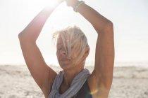Старшая белая женщина, занимающаяся спортом на пляже в солнечный день, практикующая йогу, стоящая в позе дерева с закрытыми глазами. — стоковое фото