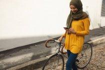Mulher de raça mista vestindo hijab e jumper amarelo para fora e sobre em movimento na cidade, usando seu smartphone sorrindo andando com bicicleta. Estilo de vida moderno Commuter. — Fotografia de Stock