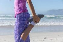 Средняя часть женщины, занимающаяся спортом на пляже в солнечный день, практикующая йогу и растягивающаяся на фоне моря. — стоковое фото