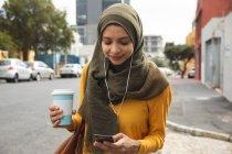Mulher de raça mista vestindo hijab e jumper amarelo para fora e sobre em movimento na cidade, segurando takeaway café usando smartphone com fones de ouvido em. Estilo de vida moderno Commuter. — Fotografia de Stock