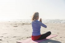 Белая женщина с светлыми волосами, наслаждающаяся тренировками на пляже в солнечный день, практикующая йогу и сидящая в позиции йоги. — стоковое фото