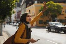 Mulher de raça mista vestindo hijab e jumper amarelo para fora e sobre em movimento na cidade, parando táxi com braço no smartphone segurando ar usando fones de ouvido sem fio. Estilo de vida moderno Commuter. — Fotografia de Stock