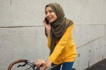 Mulher de raça mista vestindo hijab e jumper amarelo para fora e sobre em movimento na cidade, falando em seu smartphone sorrindo sentado em bicicleta. Estilo de vida moderno Commuter. — Fotografia de Stock