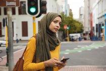 Mulher de raça mista vestindo hijab e jumper amarelo para fora e sobre em movimento na cidade, segurando seu smartphone. Estilo de vida moderno Commuter. — Fotografia de Stock
