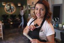 Портрет кавказької жінки-перукарки, що працює в перукарні, тримає ножиці і гребінець, посміхається і позує для фотографії. Здоров