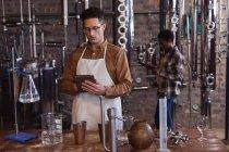 Кавказький робітник одягнений в фартух, використовуючи цифрову табличку на джинській винокурні. Виробництво алкоголю і фільтрація. — стокове фото