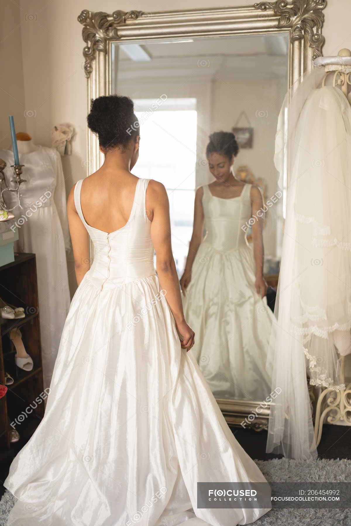 70371da0954 Young bride in a wedding dress looking into mirror at boutique — Stock  photos