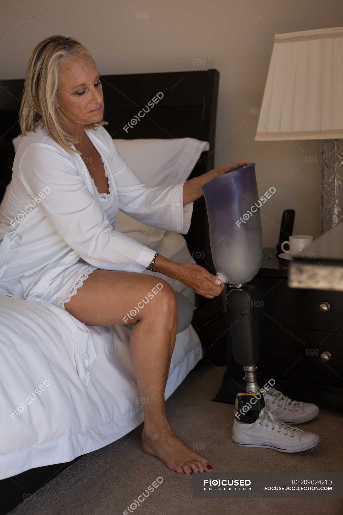 Mature women legs Mature Woman Holding Prosthetic Leg In Bedroom At Home Physical Impairment Authentic Stock Photo 209024210