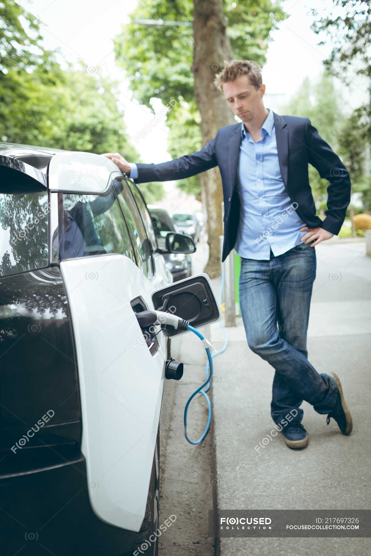 Young Businessman Charging Electric Car At Charging Station Energy Source People Stock Photo 217697326