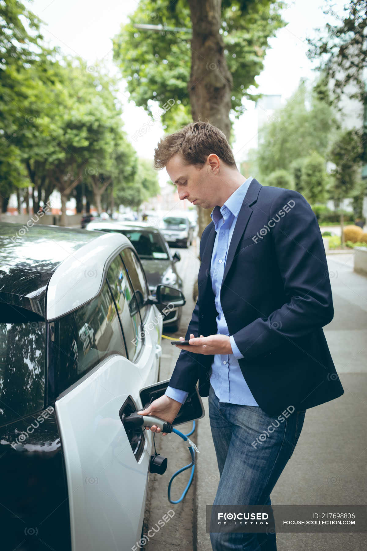 Businessman Using Mobile Phone While Charging Electric Car At Charging Station Electricity Power Supply Stock Photo 217698806