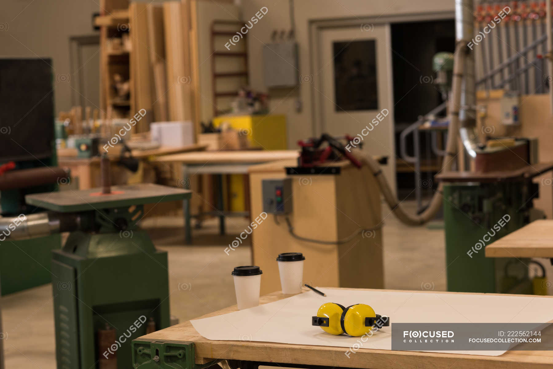 blueprint with earmuffs and disposable cups on table in