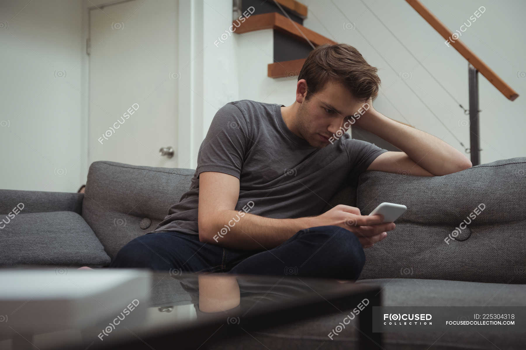 Man Using Mobile Phone On Sofa At Home