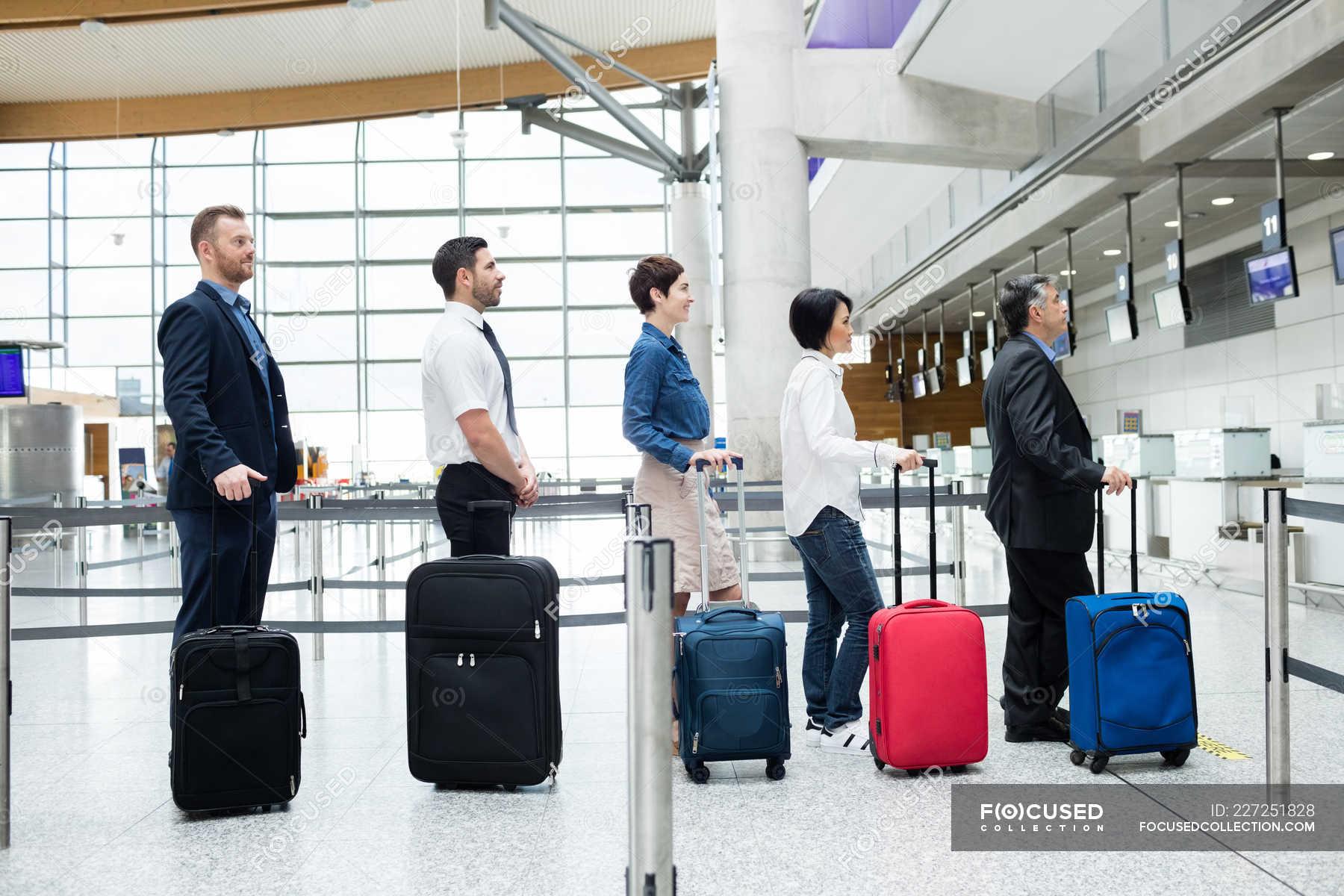 Пассажиров, ожидающих в очереди у стойки регистрации с багажом в ...