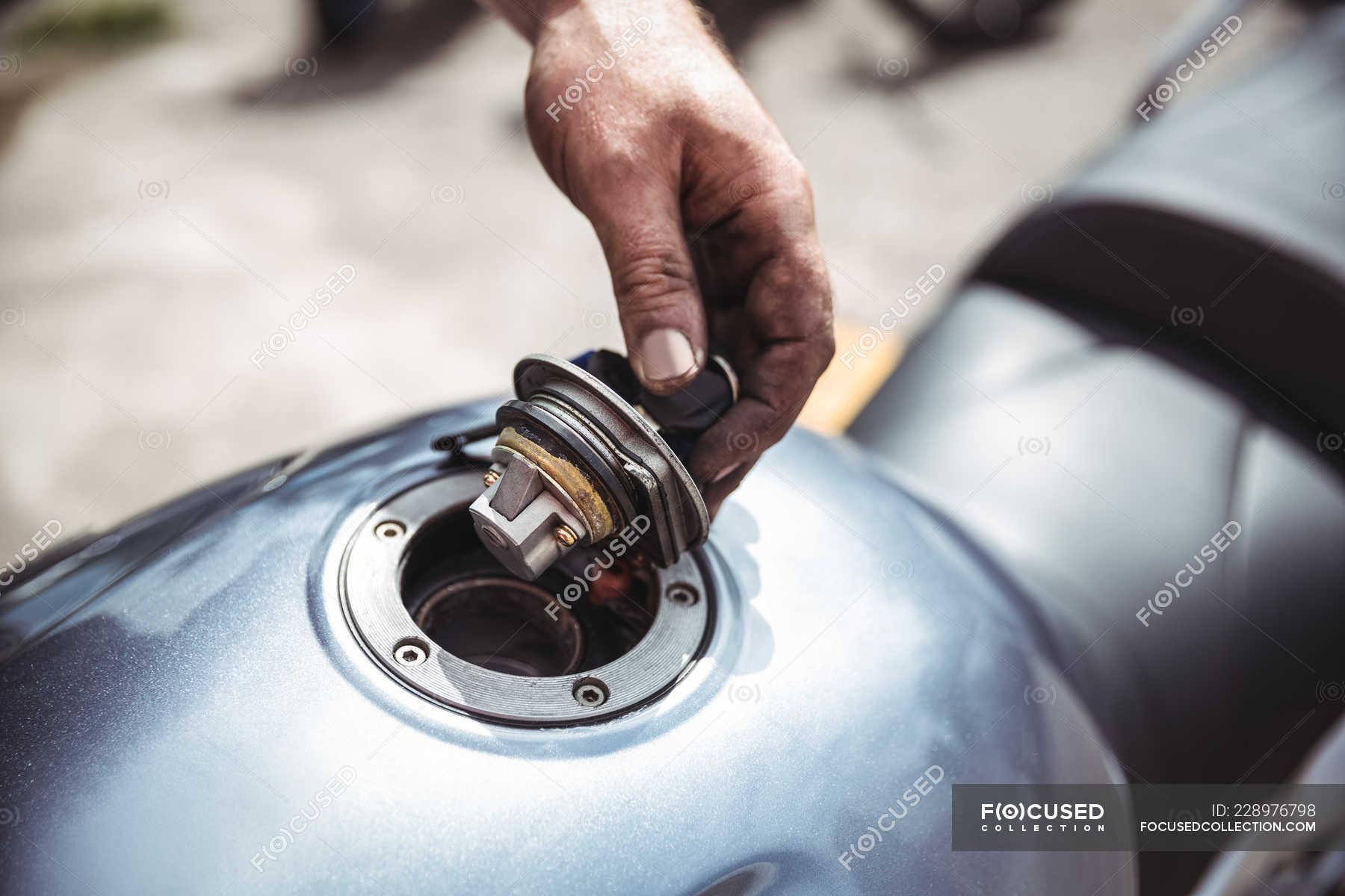 Hand of mechanic opening fuel tank of motor bike at workshop