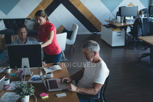 Деловые коллеги обсуждают за компьютером в офисе — стоковое фото