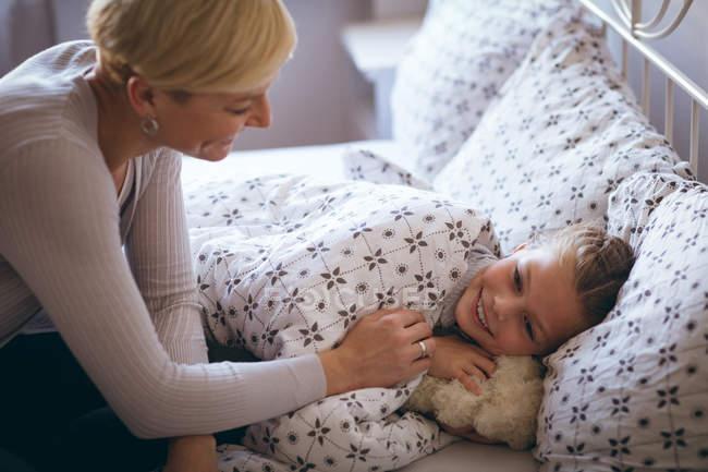 Madre despierta a su hija en la mañana en casa - foto de stock