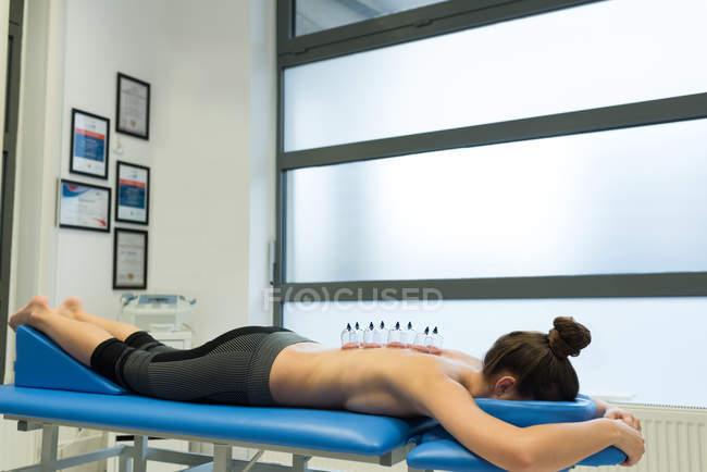 Donna sdraiata sul petto con terapia di coppettazione sulla schiena in clinica — Foto stock
