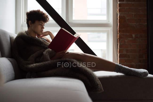Женщина читает книгу, отдыхая на диване в гостиной — стоковое фото