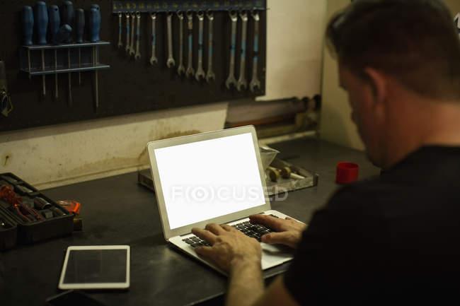 Задній вид механік, використовуючи ноутбук у гаражі — стокове фото