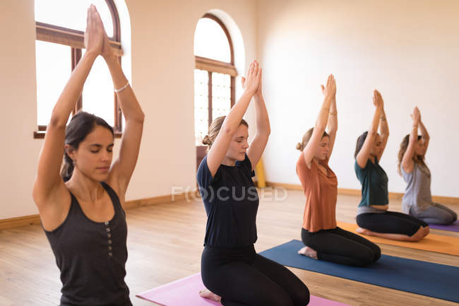 Group of women meditating together in fitness club — Stock Photo