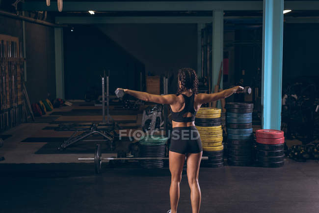 Rear view of fit woman exercising with dumbbells in the gym — Stock Photo