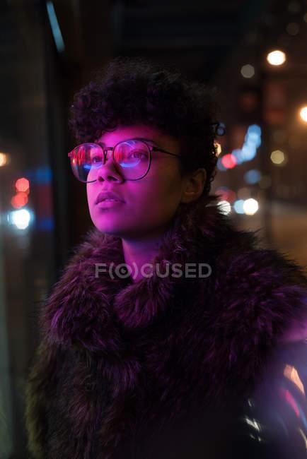 Задумчивая женщина, стоящая ночью на улице — стоковое фото
