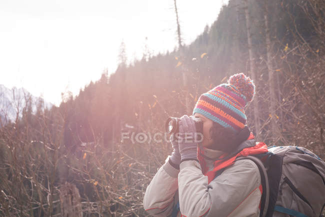 Rear view of woman taking picture with digital camera during winter — Stock Photo