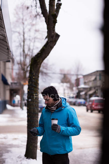 Man using mobile phone in town during winter — Stock Photo