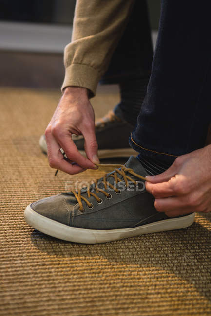 Low section of man tying shoelaces in living room at home — Stock Photo