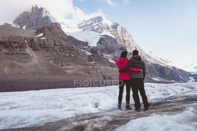 Couple standing together with arm around near mountain — Stock Photo