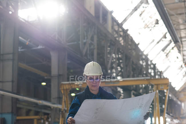 Female technician looking at blue print in metal industry — Stock Photo