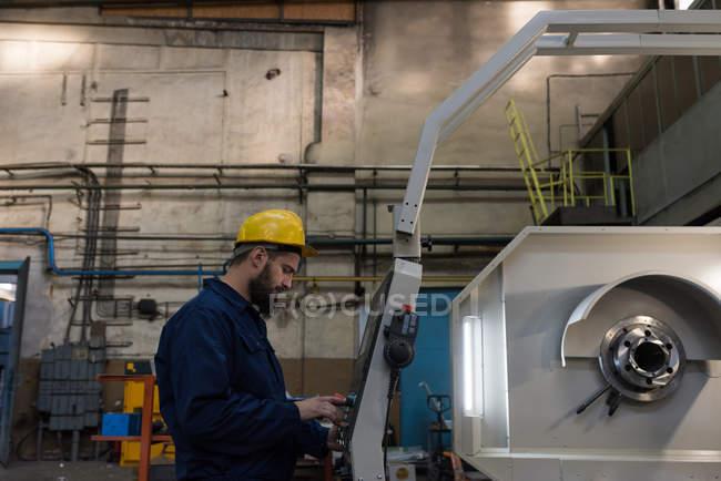 Técnico atento que opera la máquina en la industria del metal - foto de stock