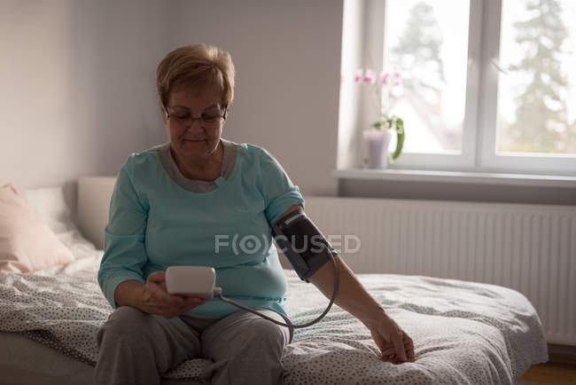 Senior woman checking blood pressure on a monitor at home — Stock Photo