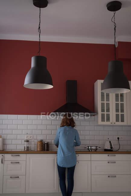 Взгляд сзади на женщину, работающую на кухне дома — стоковое фото