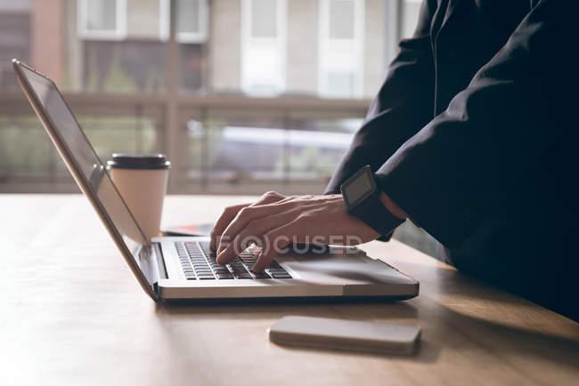 Seção intermediária do executivo trabalhando no laptop no escritório — Fotografia de Stock