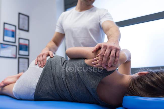 Fisioterapista che restituisce massaggio alla donna in clinica — Foto stock