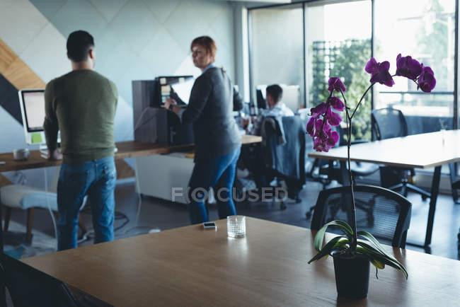 Collègues de travail interagissent entre eux tout en travaillant au bureau — Photo de stock
