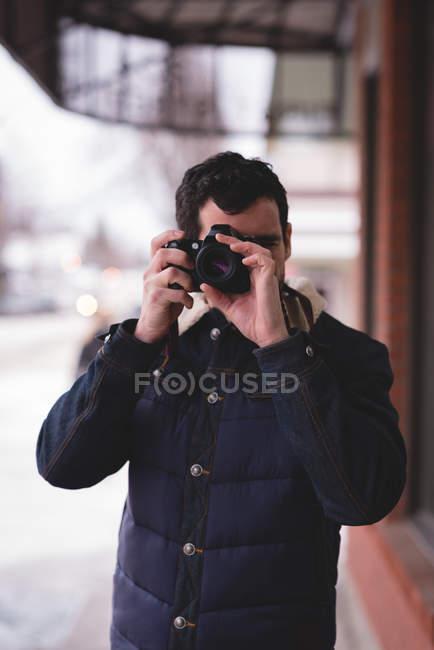 Людина, натиснувши фото з цифрової камери за межами магазину — стокове фото