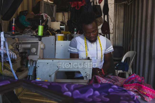 Tailor sewing clothes on sewing machine at shop — Stock Photo