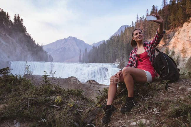Young woman taking selfie with mobile phone near waterfall — Stock Photo