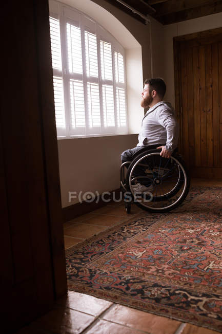 Disabled man in wheelchair looking through window at home — Stock Photo